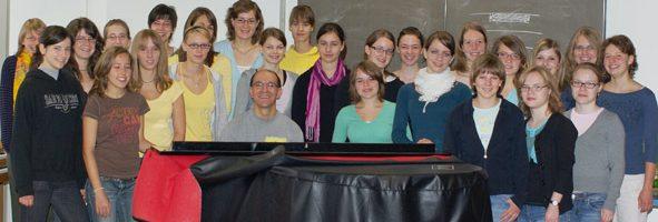 Unser Musikschulleiter Gerd Clauss am Klavier umgeben von Jugendlichen bei einem Projekt am Gymnasium Neckartenzlingen.